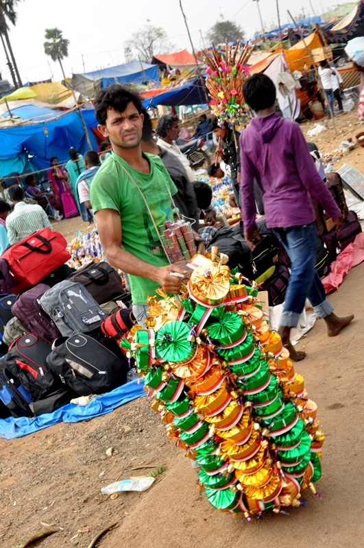 A vendor selling 'Whistle Caps' at Medaram Jathara